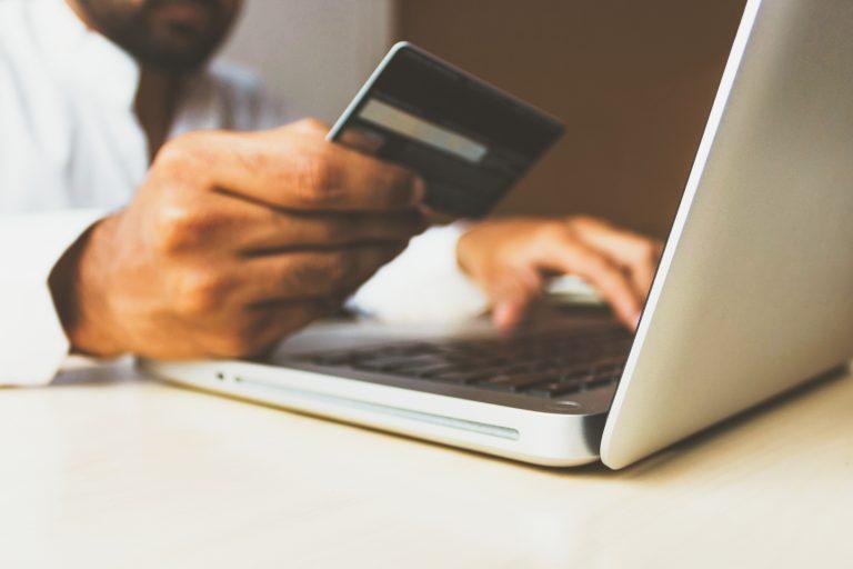 man holding credit card near laptop
