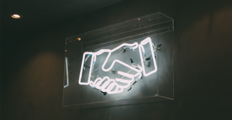 neon sign of a handshake