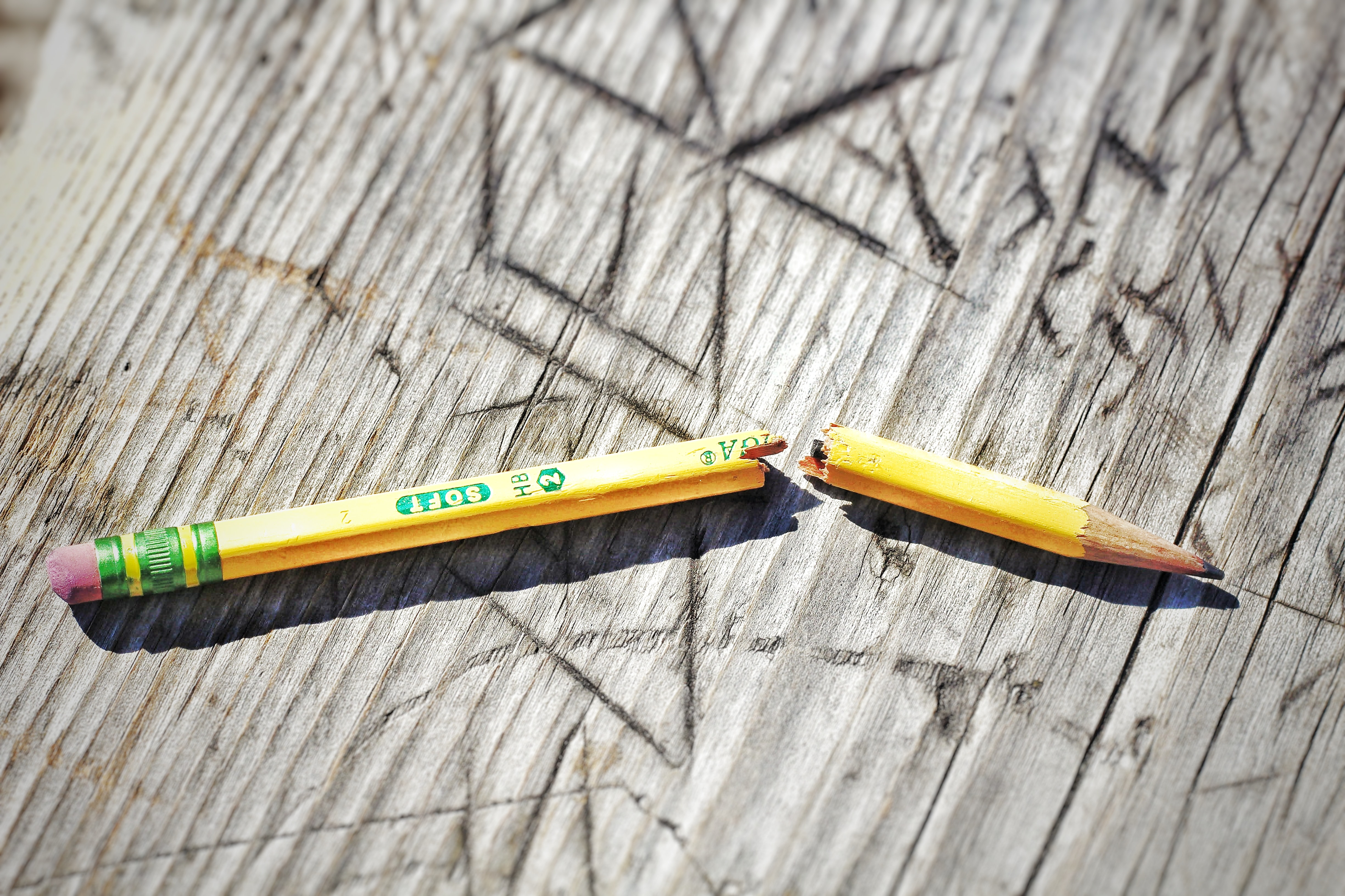 yellow broken pencil on wood background