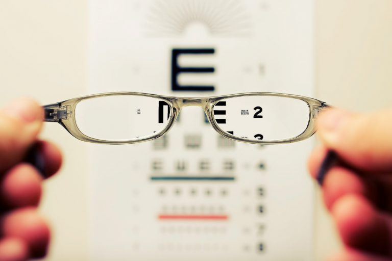 glasses-lens-in-focus-of-blurred-text-background